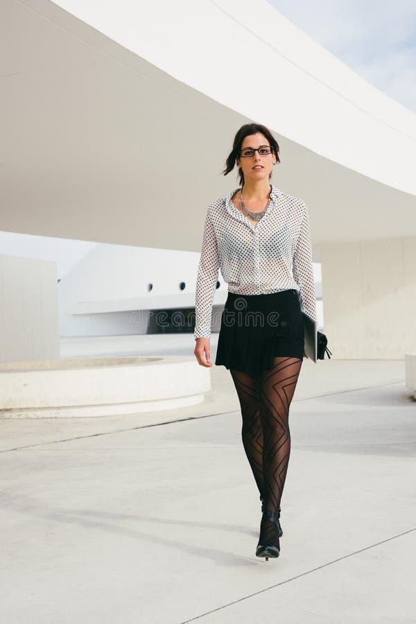Moderne Berufsfrau, die draußen geht stockbild