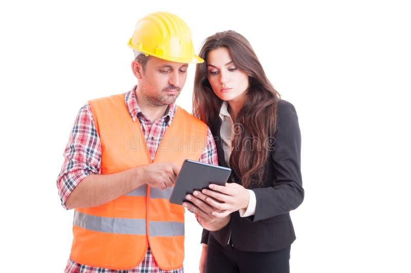 Moderne bouwer en bedrijfsvrouw die draadloze tabletpc met behulp van stock foto