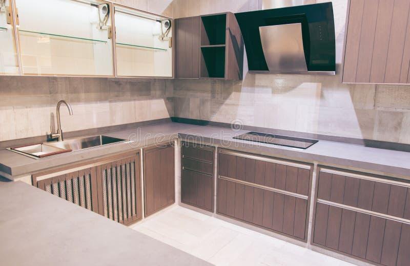 Moderne braune Küche kennzeichnet die dunkelbraunen flachen vorderen Kabinette, die mit grauen Quarz Countertops zusammengepaßt w stockbild