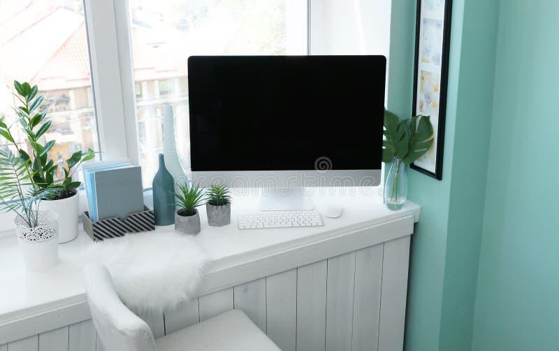 Moderne comfortabele werkplaats met computer op venstervensterbank royalty-vrije stock foto's