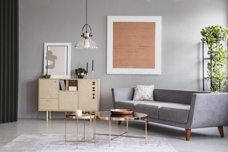 Moderne Couch- und Kupfertabellen in einem grauen Wohnzimmerinnenraum mit einer Malerei Reales Foto stockfotografie