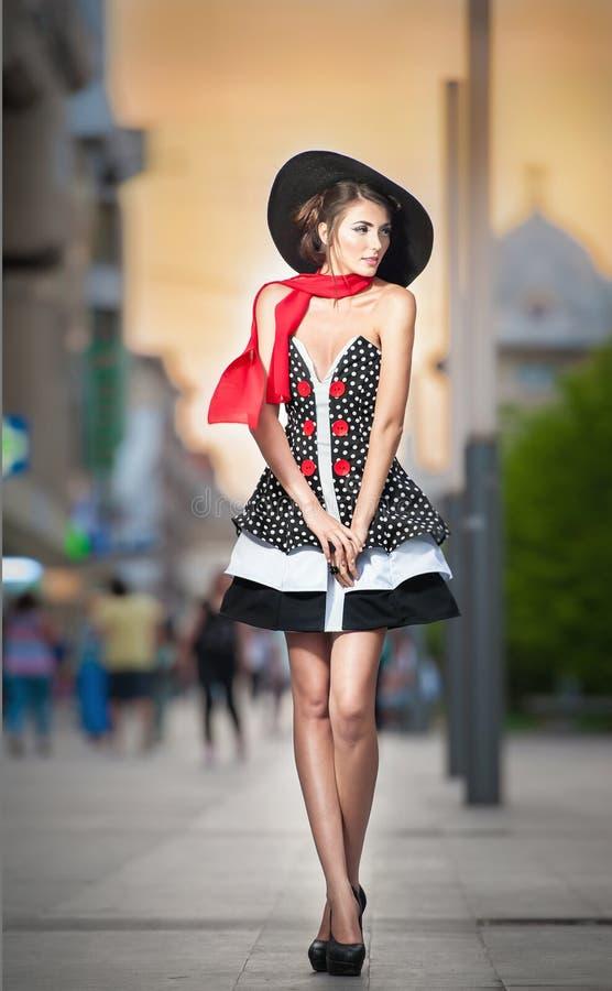 Moderne Dame, die den schwarzen Hut aufwirft auf der Straße trägt lizenzfreies stockbild