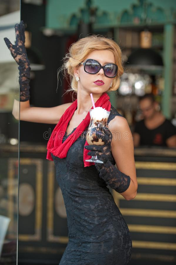 Moderne Dame mit kurzem schwarzem Spitzekleid und roter Schal und hohe Absätze, Außenaufnahme Junge attraktive kurzhaarige Blondi lizenzfreie stockfotografie