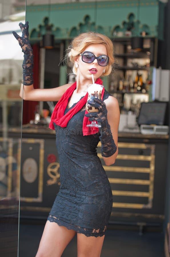 Moderne Dame mit kurzem schwarzem Spitzekleid und roter Schal und hohe Absätze, Außenaufnahme Junge attraktive kurzhaarige Blondi stockfoto