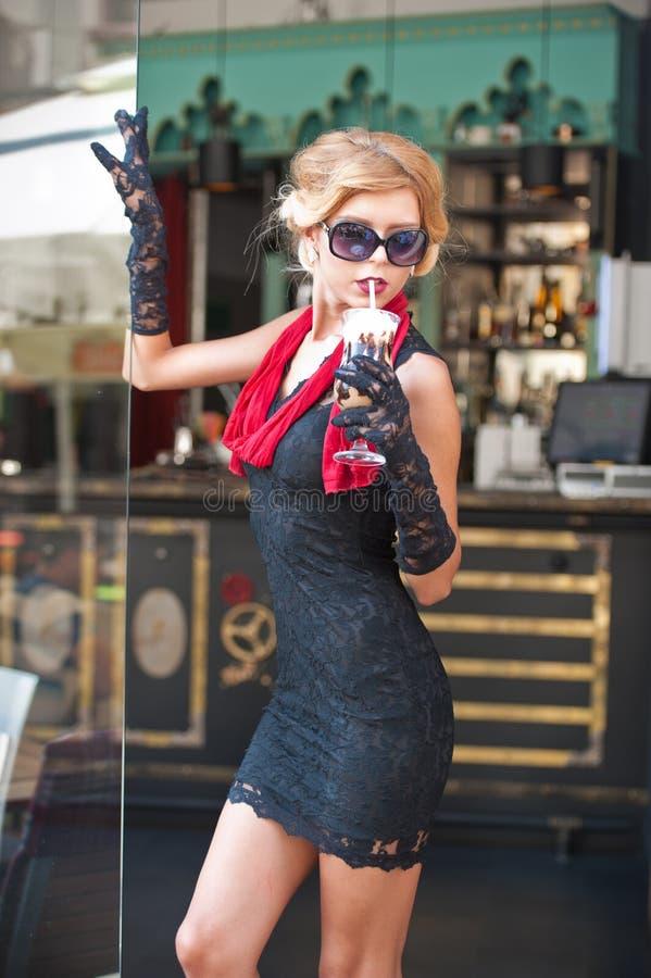 Moderne Dame mit kurzem schwarzem Spitzekleid und roter Schal und hohe Absätze, Außenaufnahme Junge attraktive kurzhaarige Blondi lizenzfreies stockfoto