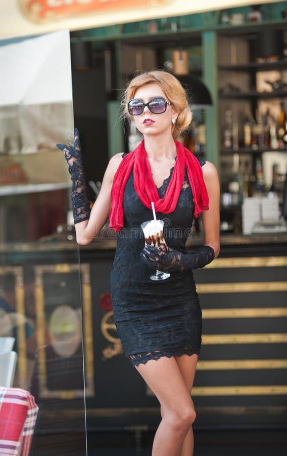 Moderne Dame mit kurzem schwarzem Spitzekleid und roter Schal und hohe Absätze, Außenaufnahme Junge attraktive kurzhaarige Blondi lizenzfreie stockbilder