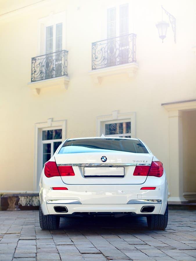 Moderne de auto achter achterdiemening van luxebmw 750Li XDrive bij steen het bedekte parkeren dichtbij oud huis met balkons met  royalty-vrije stock fotografie