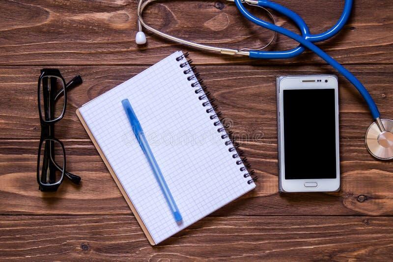 Moderne die arts ` s op de lijst wordt geplaatst De zaken plaatsten voor het ziekenhuis: glazen, telefoon, medische apparatuur, n stock foto