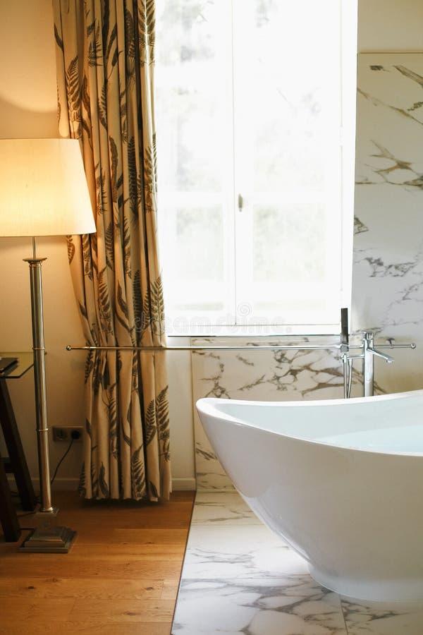 Moderne die badkamers met staande lamp en marmeren muur wordt verlicht royalty-vrije stock foto's