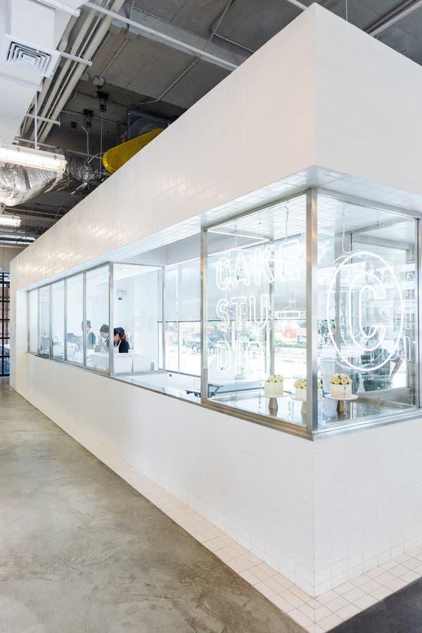 Moderne die gebakjekeuken in wit en glazen venster met productielijn, gebakje en cake die showcase maken door gebakjechef-koks wo stock afbeelding
