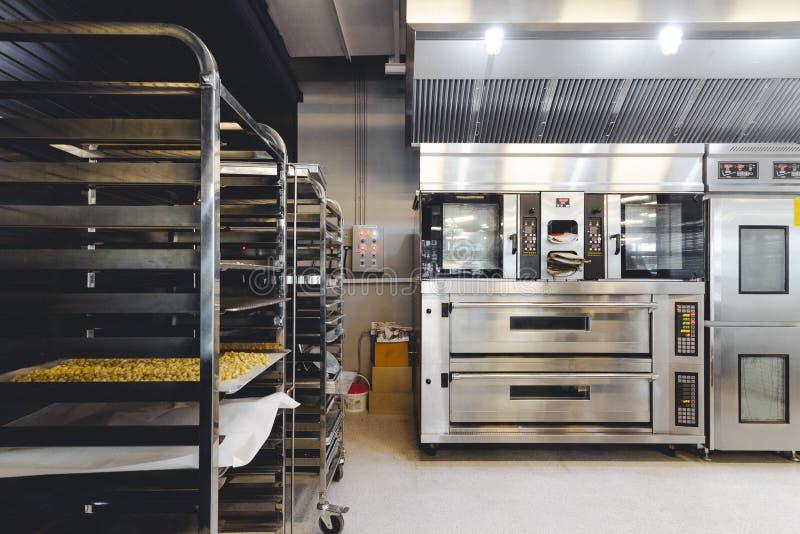 Moderne die gebakjekeuken in zwarte, wit en staal met bakselmachine wordt verfraaid, oven, transportband, productielijn, mixer stock foto's