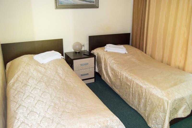 Moderne dubbele ruimte met twee eenpersoonsbedden, bedlijst, handdoeken en schemerlamp, comfortabele goedkope ruimte voor reizige stock fotografie