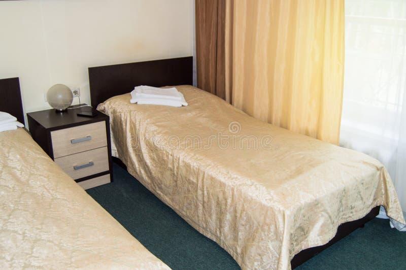 Moderne dubbele ruimte met twee eenpersoonsbedden, bedlijst, handdoeken en schemerlamp, comfortabele goedkope ruimte voor reizige stock foto