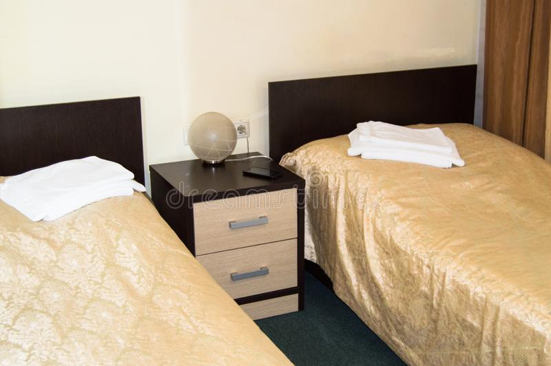 Moderne dubbele ruimte met twee eenpersoonsbedden, bedlijst, handdoeken en schemerlamp, comfortabele goedkope ruimte voor reizige royalty-vrije stock afbeelding