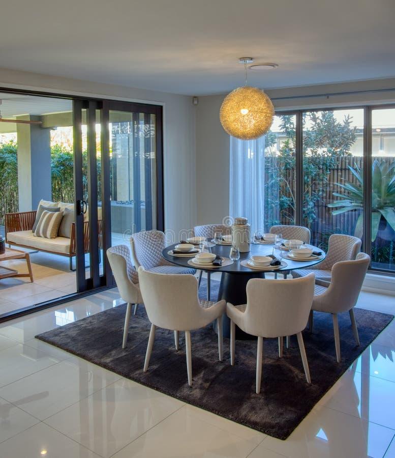 Moderne eetkamer met acht stoelen naast openluchtzittingsgebied in de open lucht royalty-vrije stock afbeeldingen