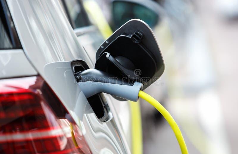Moderne elektrische auto die met machtskabel belasten stock afbeeldingen