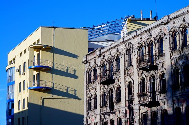 Moderne et façade d'un vieux bâtiment délabré contre un ciel bleu photographie stock