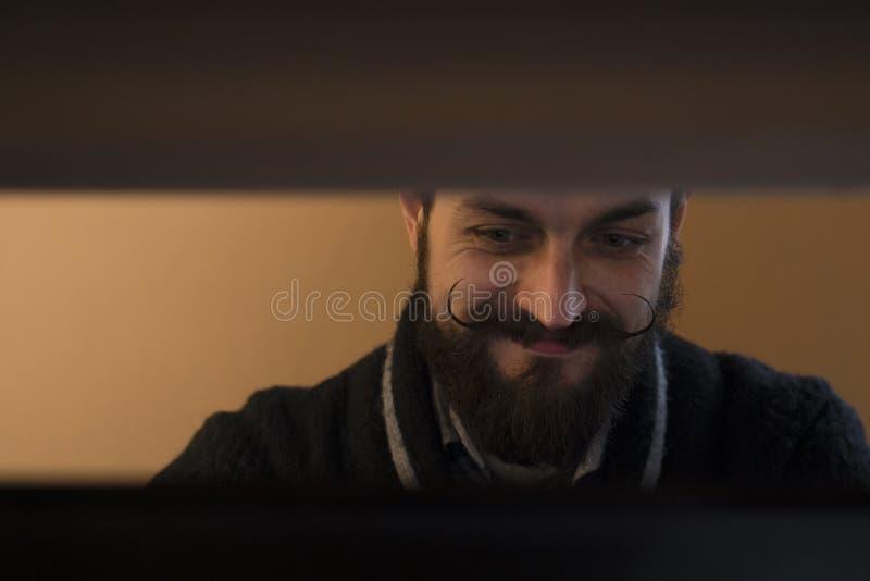 Moderne, Expressieve Gebaarde Bureaubediende die met Mustages met Notitieboekje op Kantoor werken stock foto