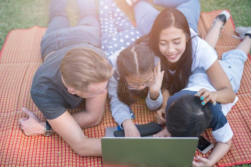 Moderne familie die laptop met behulp van terwijl het rusten in park stock foto