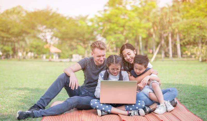 Moderne familie die laptop met behulp van terwijl het rusten in park stock fotografie