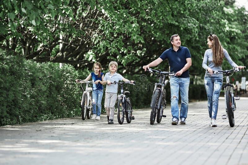 Moderne familie met hun fietsengang door het stadspark stock fotografie