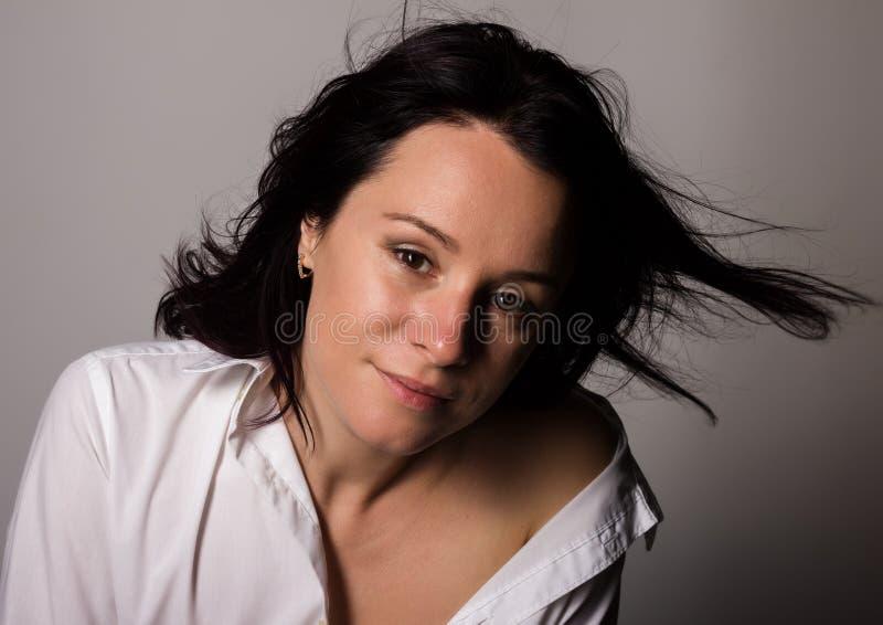 Moderne Frau in a bemannt weißes Hemd mit bloßer Schulter auf einem grauen Hintergrund lizenzfreies stockbild