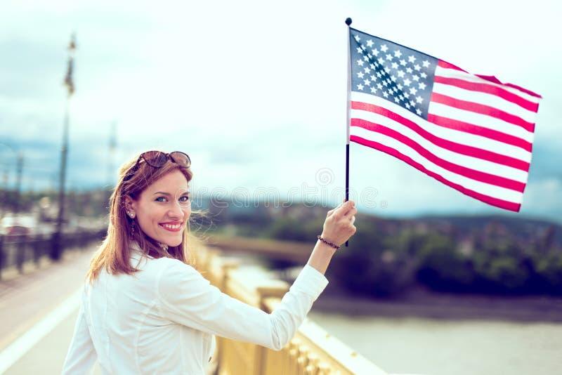 Moderne Frau des jungen Patrioten, die USA-Flagge hält stockfotos