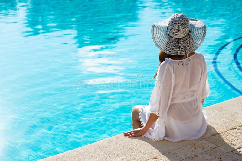 Moderne Frau, die am Poolside auf Sommerferien sich entspannt stockfoto