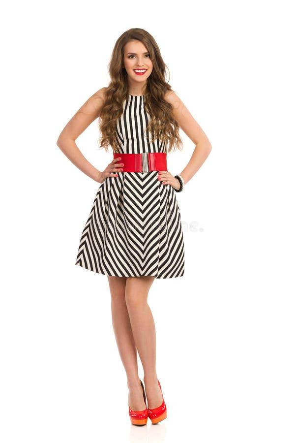 Moderne Frau in gestreiftem Kleid und in hohen Absätzen lizenzfreie stockbilder