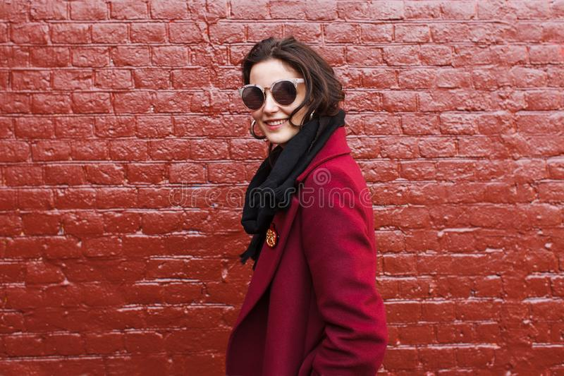 Moderne Frau im magentaroten Mantel stockfotografie