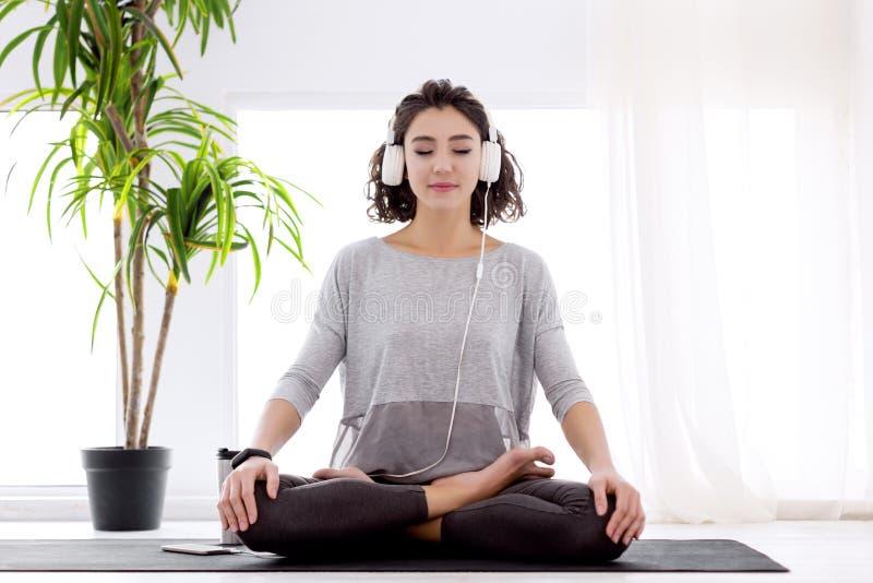 Moderne Frau mit den Kopfh?rern, die in der Yogalotoslage sitzen lizenzfreies stockfoto