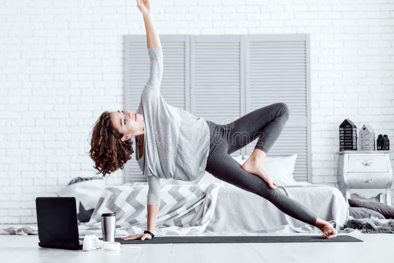 Moderne Frau mit den Kopfh?rern, die in der Yogalotoslage sitzen lizenzfreies stockbild