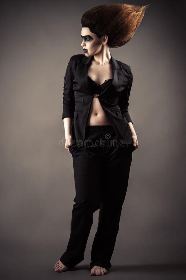 Moderne Frau mit dunklem Make-up im Anzug, der in voller Länge steht stockfoto