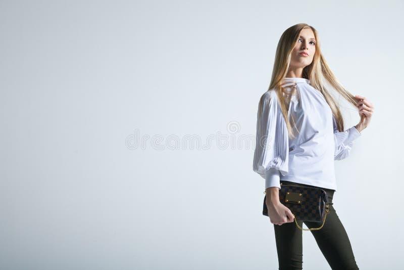Moderne Frau mit einer Tasche im hellen Hintergrund stockbild
