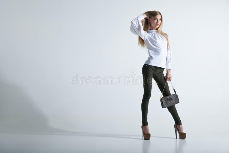 Moderne Frau mit einer Tasche im hellen Hintergrund lizenzfreie stockfotografie