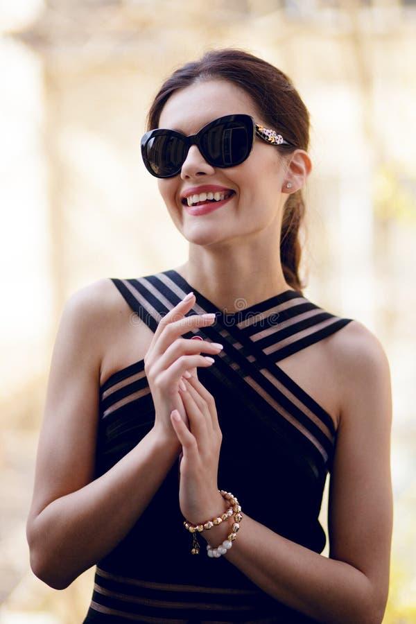 Moderne Frau mit erhabenem von, tragend in einem eleganten schwarzen Kleid und in den sunglass, in der Tageszeit, die auf Balkon  stockfotos