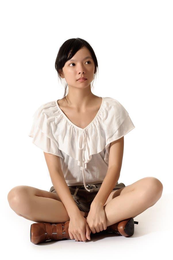 Moderne Frau sitzen auf dem Boden stockbild