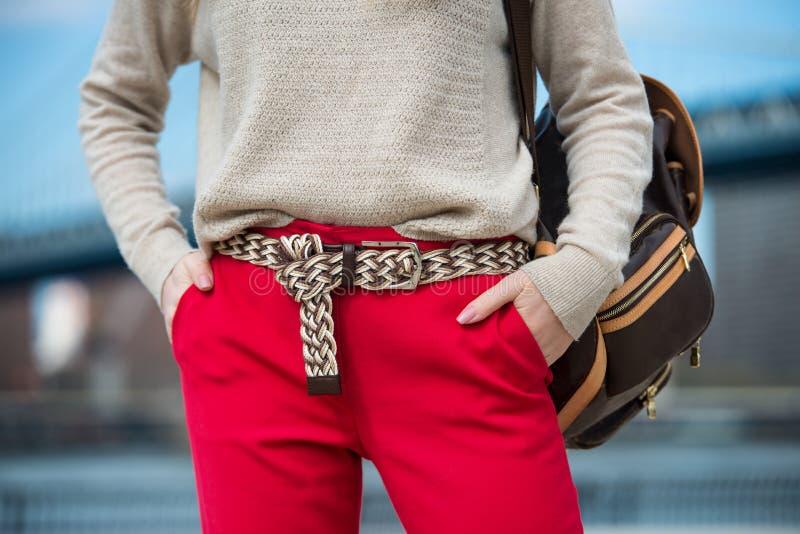Moderne Frauen ` s zufällige Frühlingsausstattung mit roten Hosen, Wolljacke, modernem Gurt und Tasche stockfoto