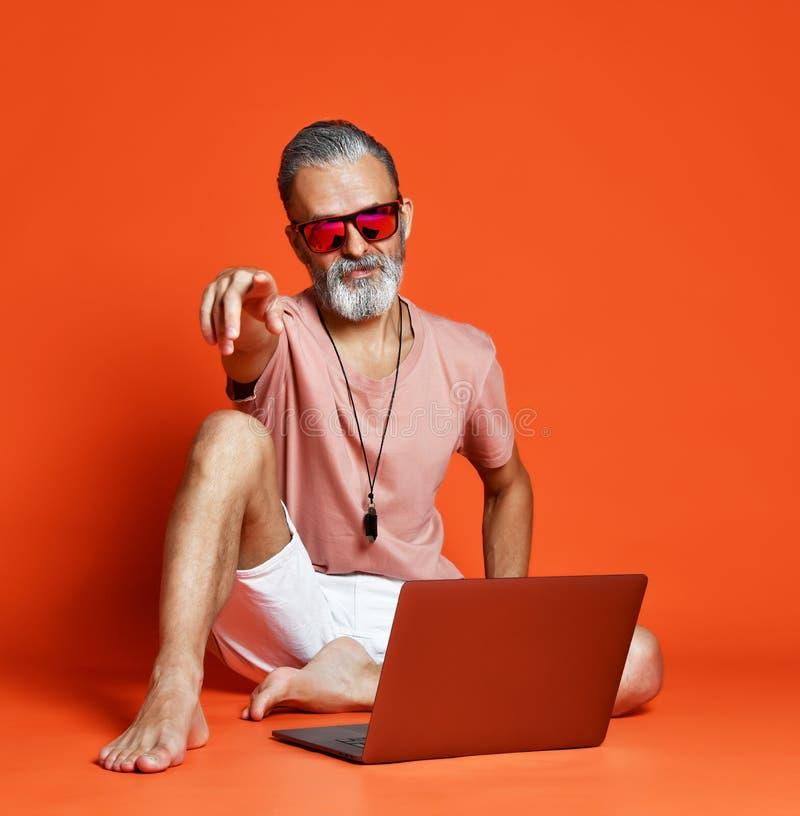 Moderne gelukkige modieuze bejaarde hogere mannelijke smeltende laptop computer royalty-vrije stock foto