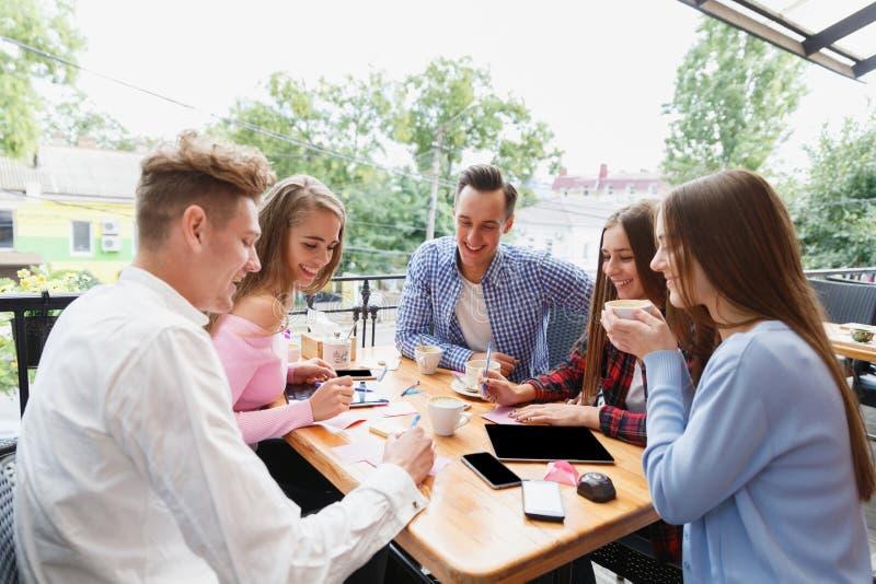 Moderne gelukkige studenten die bij de koffie aan een vage achtergrond samenwerken Actief levensstijlconcept royalty-vrije stock foto's