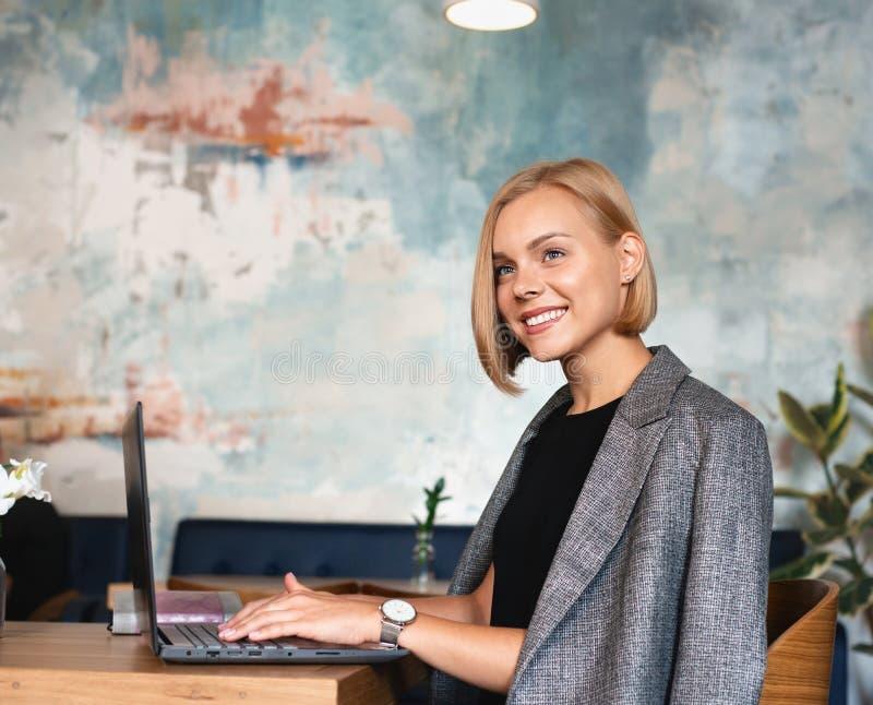 Moderne Geschäftsfrau arbeitet am Laptop-Computer im Café-Interieur stockbild