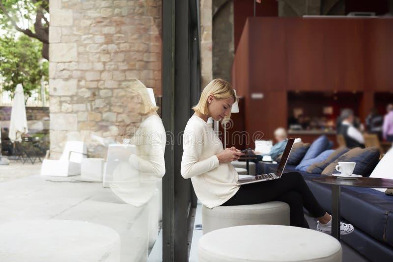 Moderne Geschäftsfrau, die an ihrem Netzbuch sitzt am Bibliotheks- oder Dachbodenstudio mit großen Fenstern arbeitet lizenzfreie stockfotos