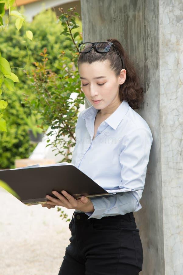 Moderne Geschäftsfrau im Büro mit Kopienraum Verwahren von Dokumenten in den Händen Dachbodenbüro des offenen Raumes lizenzfreies stockbild