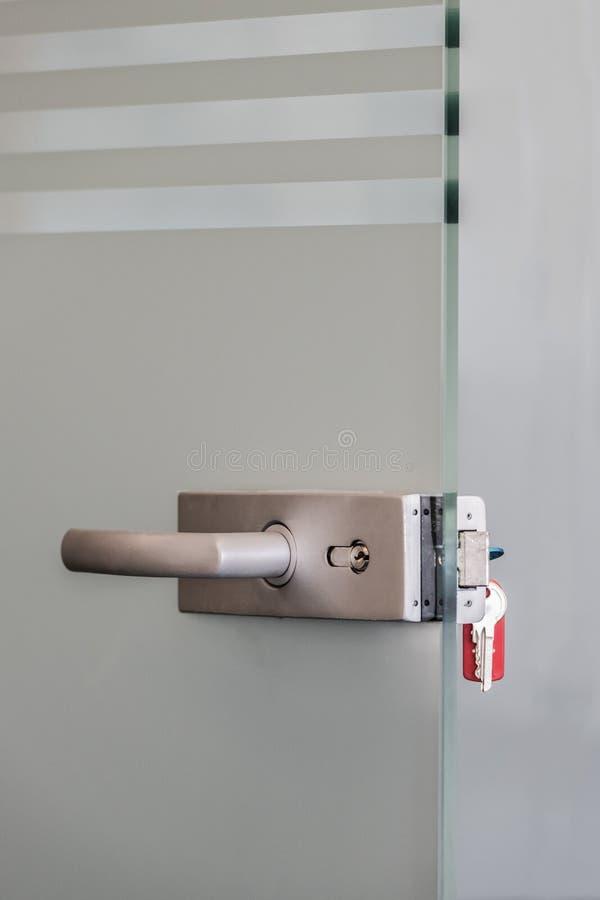 Moderne Glastür mit Metalllegierungsgriffen und -Schlüsselanhänger im Verschluss-, Ausgangs- oder Bürosicherheitskonzept lizenzfreie stockfotografie