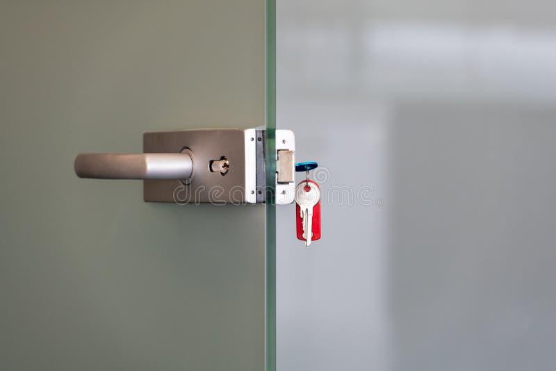 Moderne Glastür mit Metalllegierungsgriffen und -Schlüsselanhänger im Verschluss-, Ausgangs- oder Bürosicherheitskonzept stockbilder