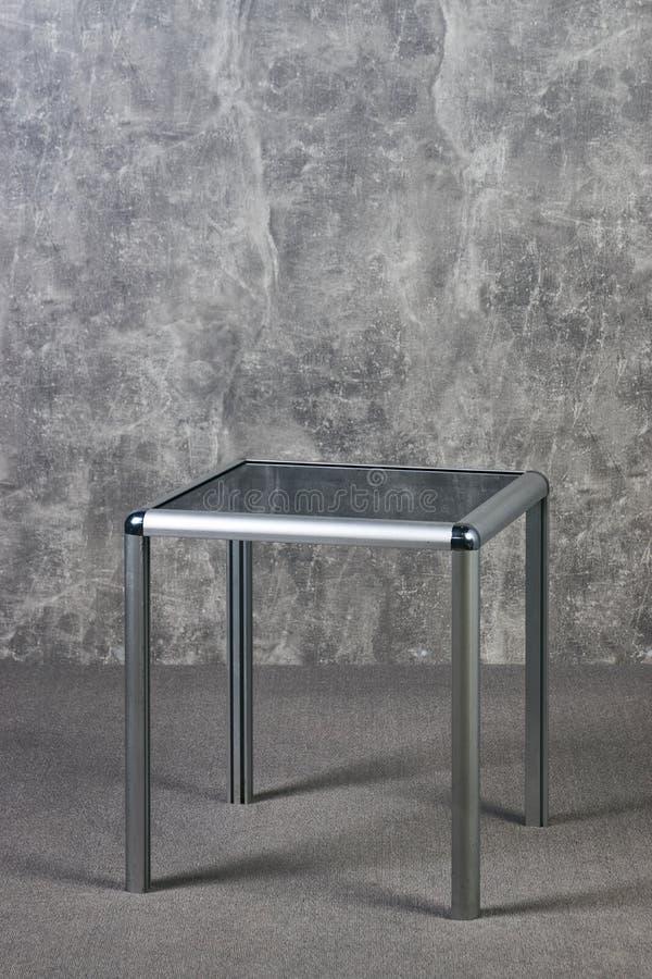 Moderne Glastischspitze auf grauem texrure Wandhintergrund stockfotografie