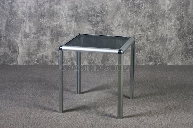 Moderne Glastischspitze auf grauem texrure Wandhintergrund lizenzfreie stockbilder