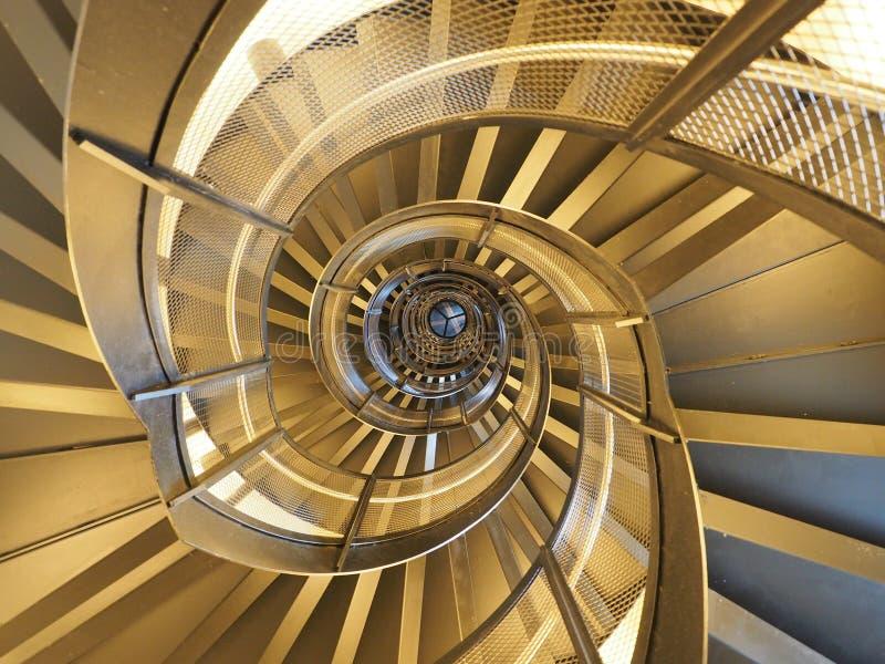 Moderne, goldene Wendeltreppe, die eine hypnotische Ansicht gibt stockbilder