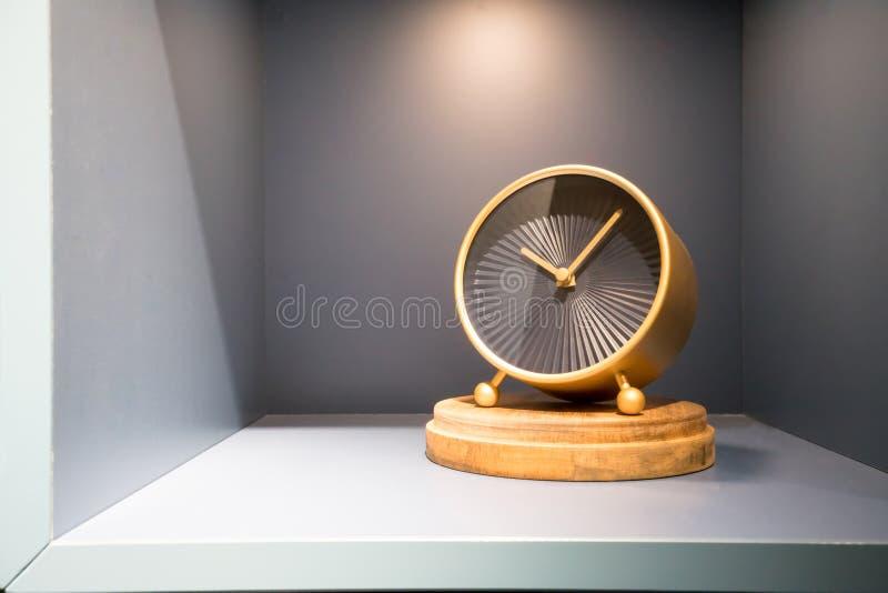 Moderne gouden en zwarte klok op grijze plankendoos voor decoratie royalty-vrije stock fotografie