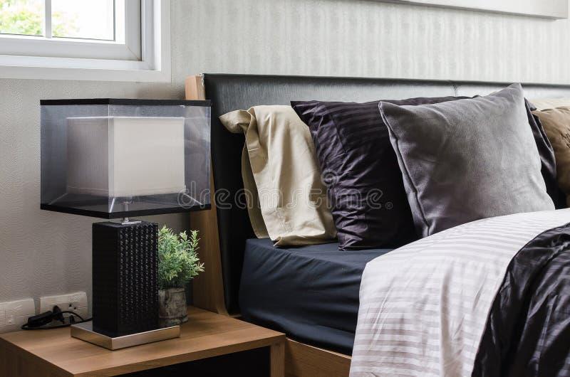 Moderne grijze slaapkamer met houten nightstand stock fotografie